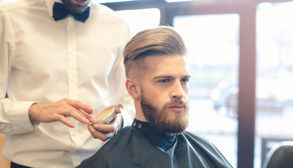 Man in barber shop applying beard wax