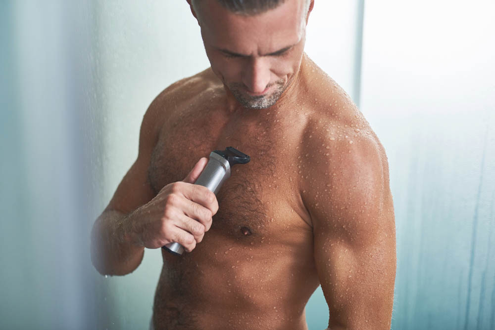 old man using electric shaver in shower